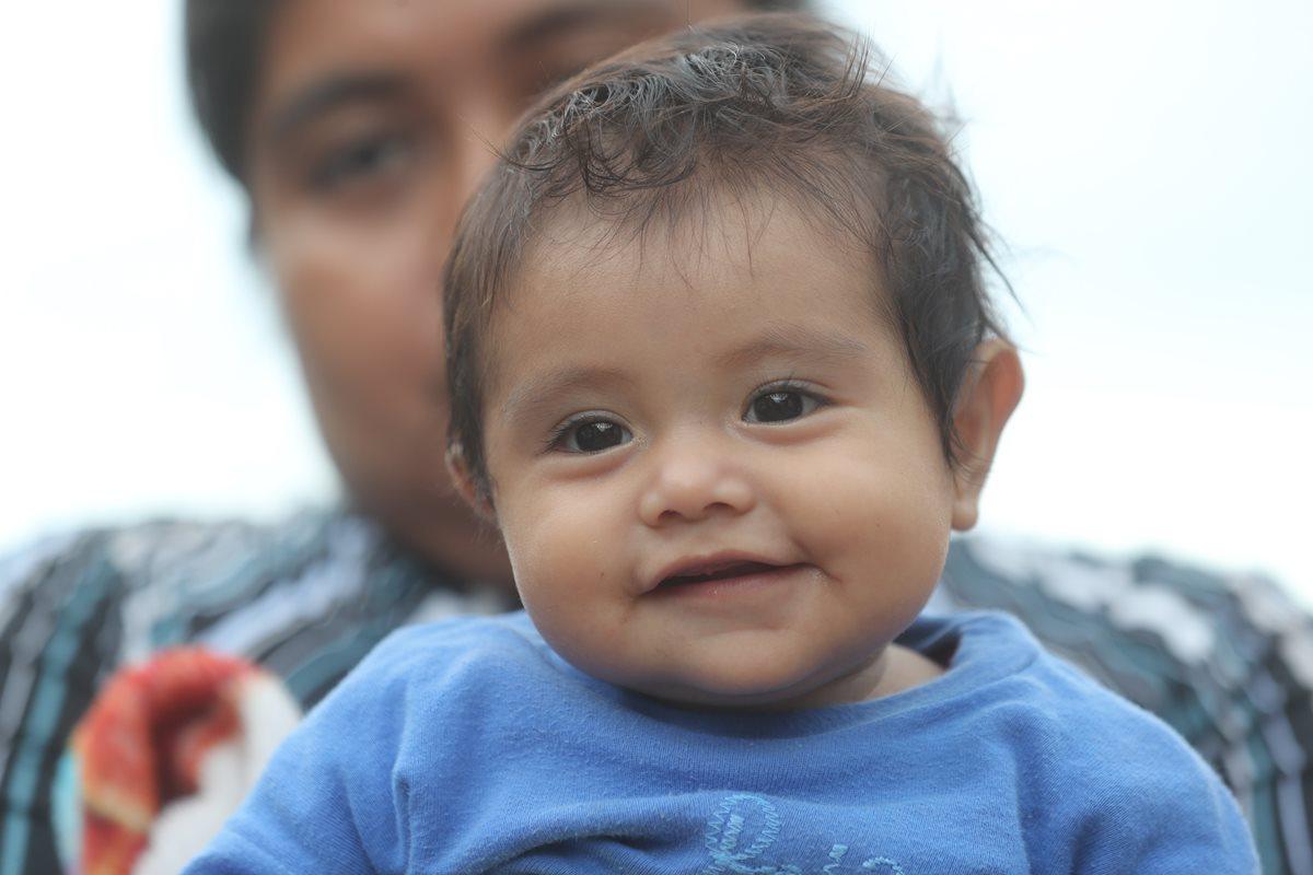Esmeralda López Pojoy, de seis meses, sonríe en brazos de su madre. La pequeña sobrevivió junto a su familia a la erupción del Volcán de Fuego. (Foto Prensa Libre: Erick Ávila)