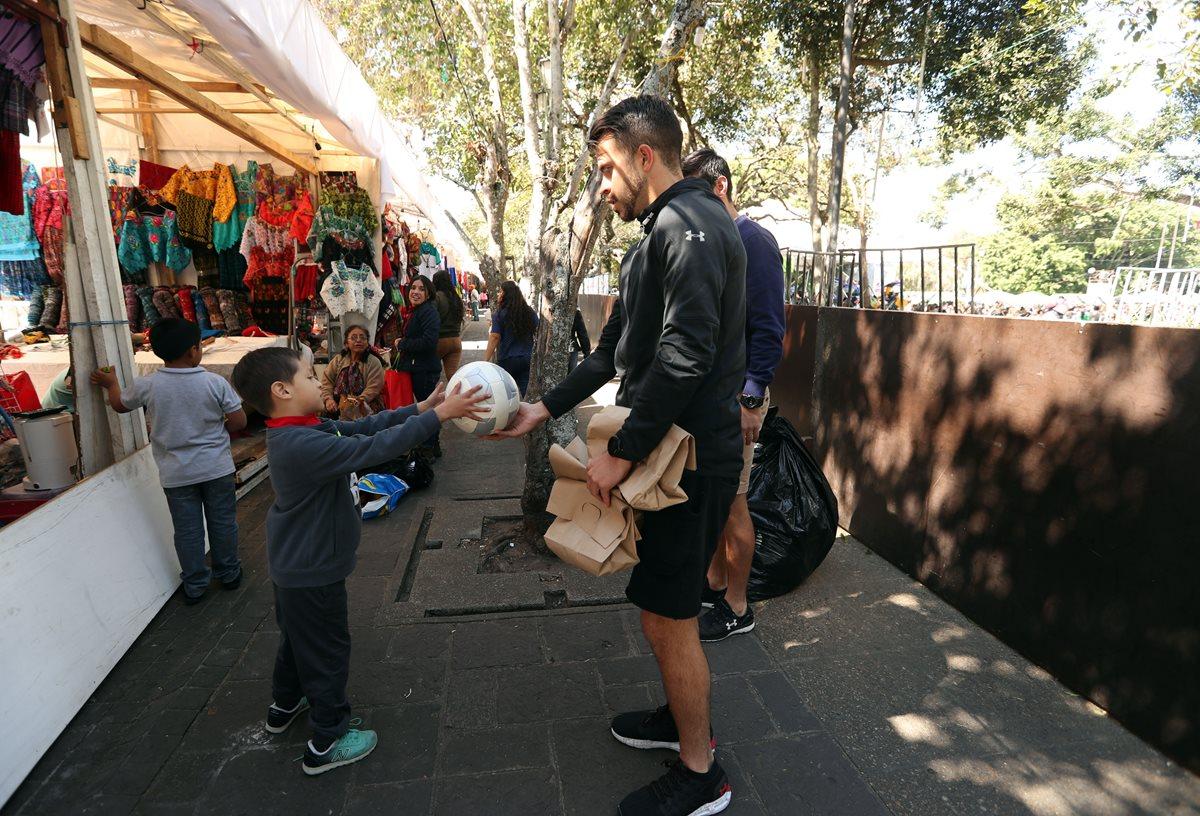 Saravia le regala un balón de futbol a un niño en zona 1. (Foto Prensa Libre: Jeniffer Gómez)
