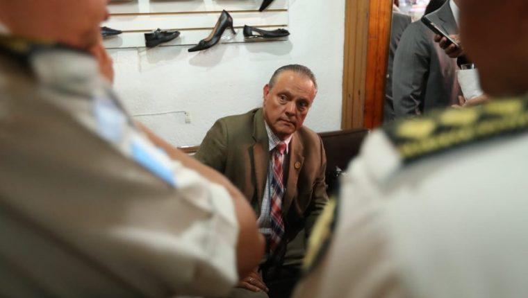 El ministro de Salud, Carlos Soto, buscó refugio en una zapatería cercana al Congreso, para resguardarse del grupo de manifestantes. (Foto Prensa Libre: Esbin García)