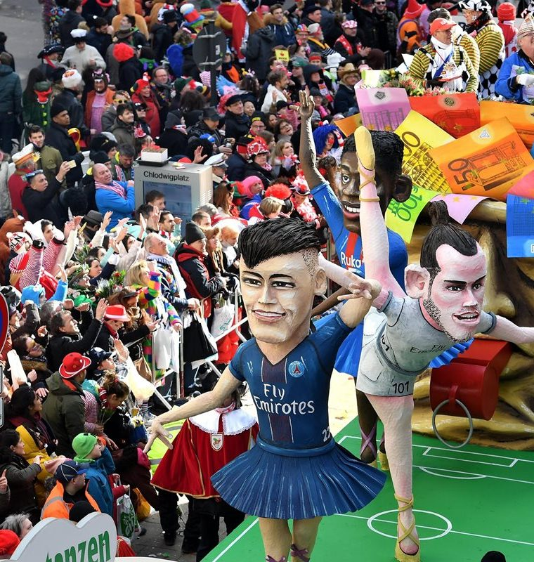 Una carroza protagonizada por el futbolista brasileño Neymar Jr., del PSG, el galés Gareth Bale, del Real Madrid, y el francés Ousmane Dembele, del FC Barcelona, participa en un desfile de carnaval en Colonia (Alemania). (Foto Prensa Libre: EFE)
