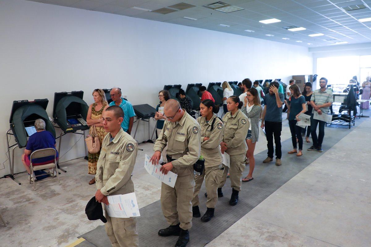 Jóvenes hacen fila durante la jornada de votación anticipada para las elecciones 2018 en Huntington Beach, California. (Foto Prensa Libre: EFE)