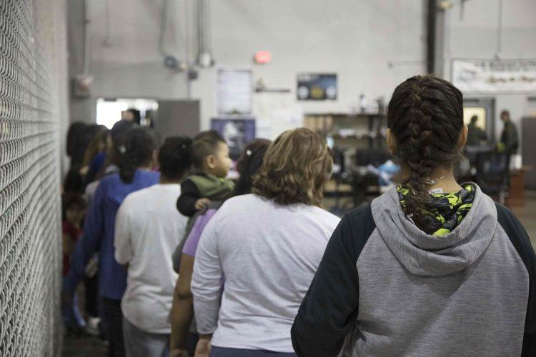 Las personas que han sido detenidas cruzando la frontera se encuentran en diferentes espacios divididos por mallas metálicas.