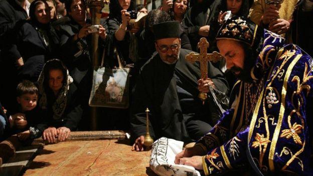 Un arzobispo sirio, que representa a una de las sectas que usan la iglesia, reza sobre la Piedra de la Deposición. GETTY IMAGES