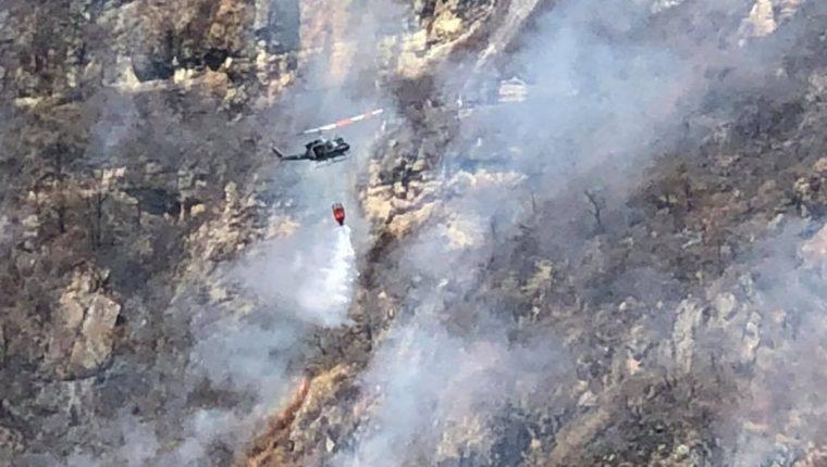 Un helicóptero vierte agua sobre un foco de incendio forestal en el volcán San Pedro. (Foto Prensa Libre: Ángel Julajuj)