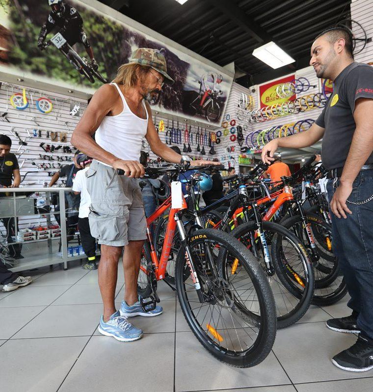 El gerente de publicidad de Bike Sport le muestra bicicletas a Antonio Paduá para que escoja la que más le convenga para desplazarse por latinoamérica. (Foto Prensa Libre: Érick Ávila)