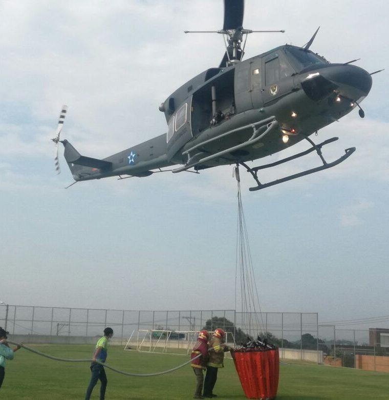 Voluntarios ayudan a cargar agua al helicóptero en el colegio Agustiniano. (Foto Prensa Libre: Cortesía Muni de Mixco)