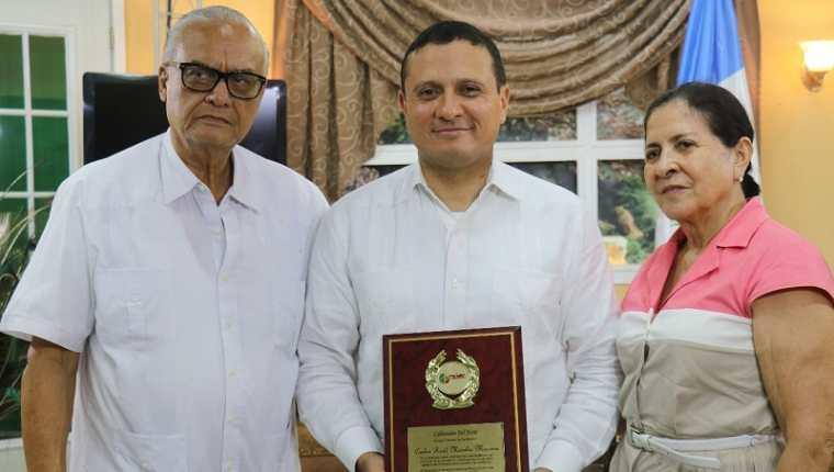 El excanciller Raúl Morales Moscoso -centro- muestra el premio recibido en Morales, Izabal, junto a sus padres Guillermo Morales Silva y Rosa Moscoso, residentes en ese municipio. (Foto Prensa Libre: Dony Stewart)