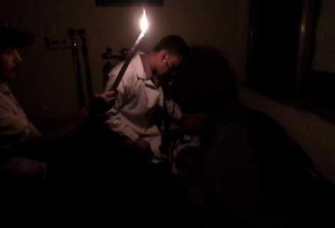 Médicos del Centro de Atención Permanente de Jacaltenango, Huehuetenango, examinan a un paciente con ayuda de una candela.