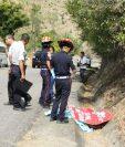 Socorristas observan el cadáver de un trabajador de Covial que fue arrollado en Sansare, El Progreso. (Foto Prensa Libre: Héctor Contreras)