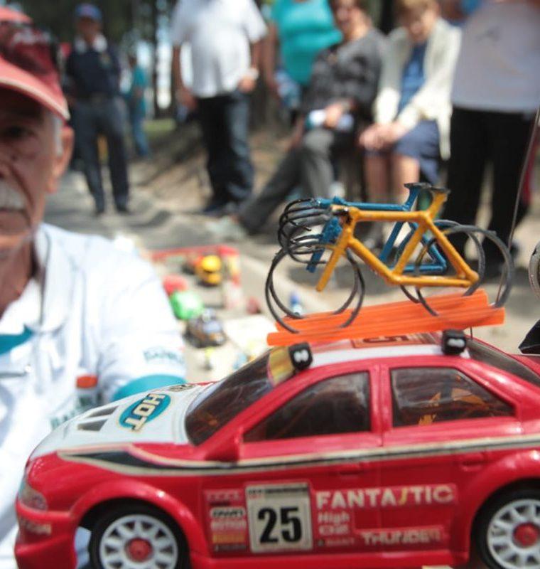 El señor Pineda Spillari muestra uno de los vehículos que lleva en el techo una bicicleta. (Foto Prensa Libre: Norvin Mendoza)