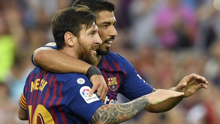 Lionel Messi celebra junto a Luis Suárez. La dupla del Barcelona fue clave en la goleada frente al Huesca. (Foto Prensa Libre: AFP)