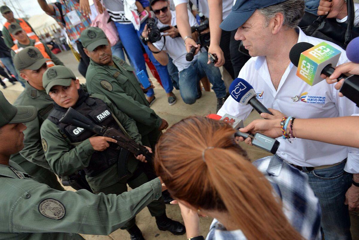 El presidente de Colombia, Juan Manuel Santos (derecha), saluda a un guardia de las fuerzas armadas de Venezuela, durante la visita que hizo a la frontera. (Foto Prensa Libre: EFE).