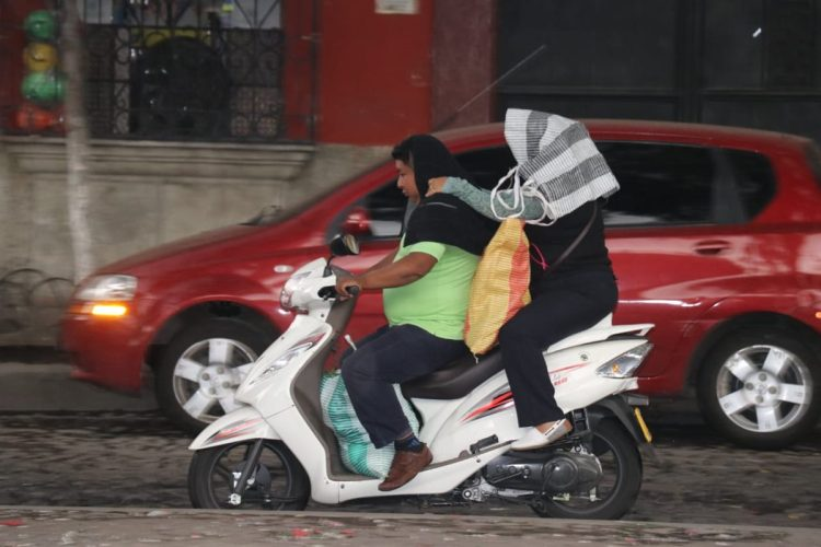 Personas cubren las vías respiratorias para no ser afectadas por la lluvia de ceniza en Sacatepéquez.