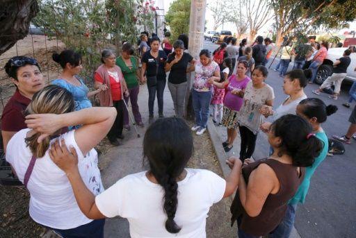La gente reza frente a la iglesia donde el sacerdote Juan Miguel Contreras donde murió. (Foto Prensa Libre: AFP)