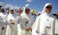Nuns attend the Mass celebrated by Pope Francis at the Plaza of the Revolution, in Holguin, Cuba, Monday, Sept. 21, 2015. Holguin's plaza was packed with thousands of people waving flags as Francis traveled in his popemobile through the crowd. Francis is the first pope to visit Holguin, Cuba's third-largest city. (Tony Gentile/Pool via AP)