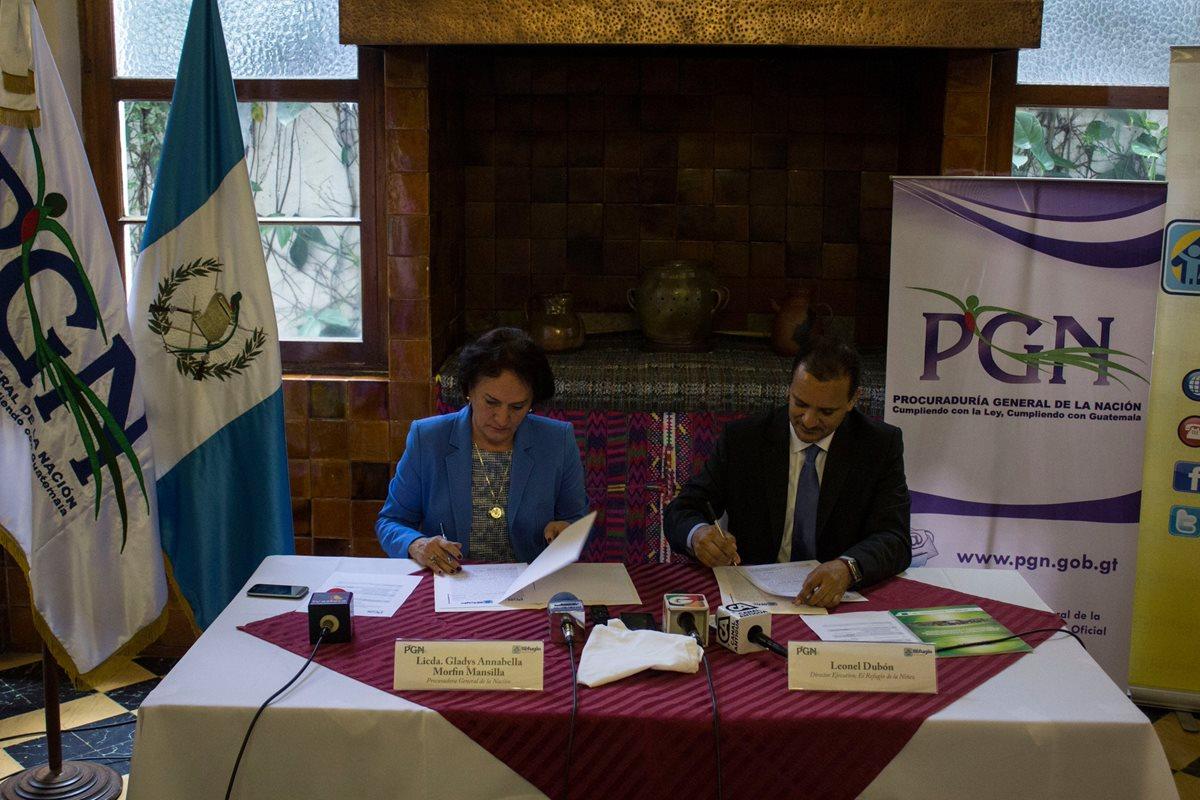 Annabella Morfín, jefa de la PGN, y Leonel Dubón, del Refugio de la Niñez, firman el convenio de cooperación. (Foto Prensa Libre: PGN)
