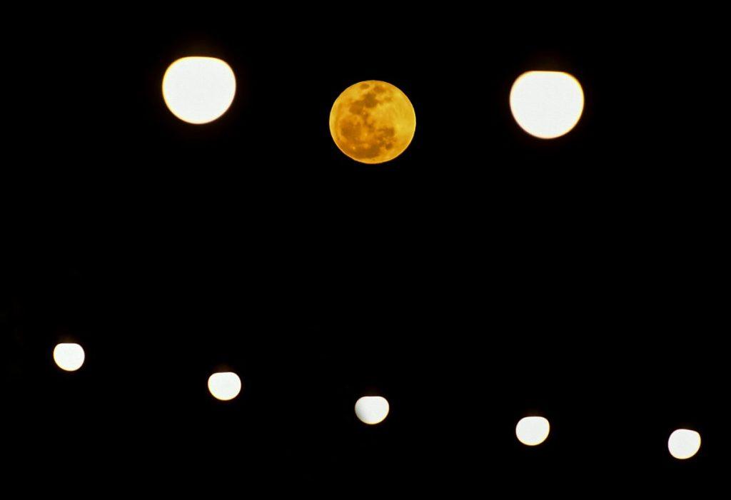 En la composición fotográfica se observa la luna llena, junto a luces de Navidad, en Panamá.
