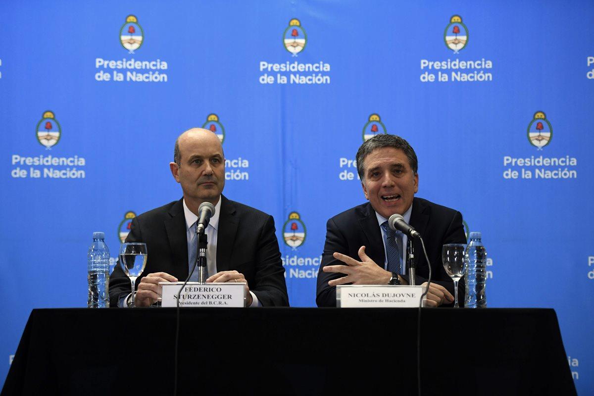 El gobernador del Banco Central de Argentina Federico Sturzenegger (i)aparece acompañado del ministro de Hacienda de Argentina, Nicolas Dujovne, durante una conferencia de prensa en Buenos Aires, Argentina. (Foto Prensa Libre:AFP).