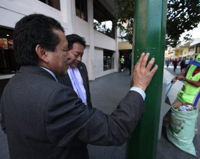 Dos personas no videntes verifican deterioro y daños a señalización para ciegos en el Paseo de la Sexta. (Foto Prensa Libre: Paulo Raquec)