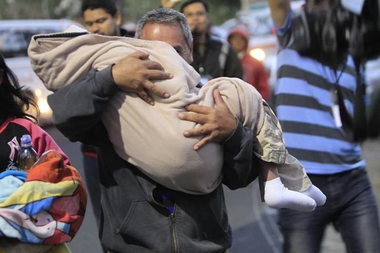Un familiar lleva en sus brazos a uno de los menores que estaba bajo protección en el Hogar Seguro, el día de la tragedia. (Foto Prensa Libre: Hemeroteca PL)