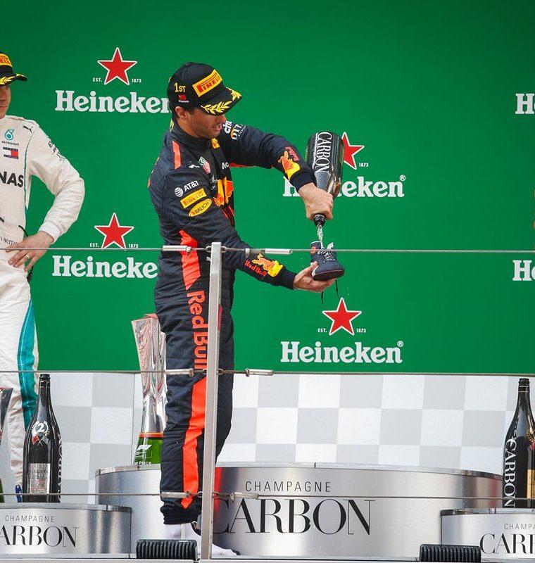 Ricciardo se sirve champán en su zapato mientras es observado por Valtteri Bottas y  Kimi Raikkonen. (Foto Prensa Libre: EFE)