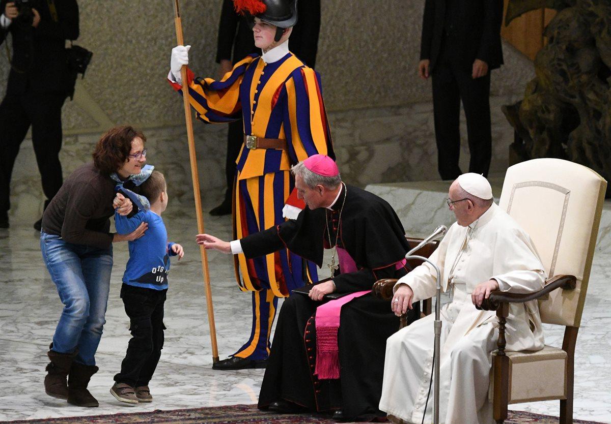 Una mujer sostiene a su hijo luego de que el pequeño de siete años corriera a saludar al papa.