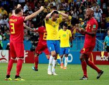 Vermaelen y Kompany celebran el pase a semifinales frente a la mirada perdida de Renato Augusto, autor del gol del descuento brasileño. (Foto Prensa Libre: EFE)