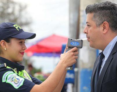 Una agente de la PMT de Mixco efectúa una prueba de alcoholemia a un conductor. (Foto Prensa Libre: Érick Ávila)