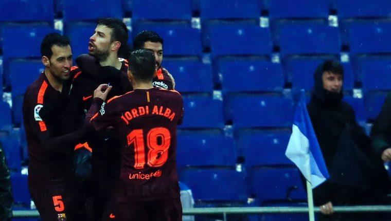 Gerard Piqué celebra junto a sus compañeros de equipo después de anotar el gol del empate contra el Espanyol. (Foto Prensa Libre: AFP)