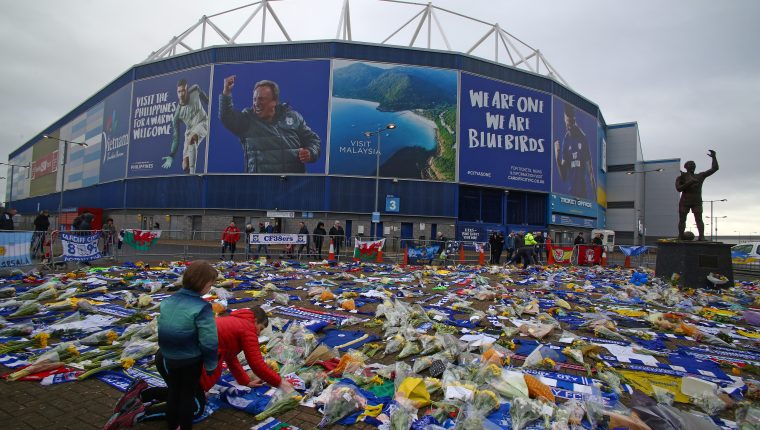 "Fans pay their respects at the display of Cardiff City scarves and jerseys, flowers, messages and other tributes to the football club's new signing Emiliano Sala, whose flight disappeared from radar over the English Channel north of Guernsey, outside the Cardiff City Stadium in Cardiff, south Wales on January 26, 2019. - Police on January 24, 2019 ended their search for Premier League player Emiliano Sala, saying the chances of finding the Argentinian alive three days after his small plane went missing over the Channel were ""extremely remote"". Their decision was met with anguished disbelief by the forward's sister Romina, who, speaking through tears, begged the search teams not to give up. The light aircraft transporting the 28-year-old striker, who signed for Cardiff City at the weekend, disappeared from radar around 20 kilometres (12 miles) north of Guernsey on the night of January 21. (Photo by GEOFF CADDICK / AFP)"