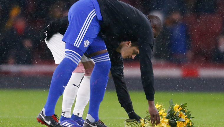 The two captain's Arsenal's German midfielder Mesut Ozil (L) and Cardiff City's Ivorian defender Sol Bamba (R) lay bunches of daffodils in honour of Cardiff City's missing Argentinian player Emiliano Sala ahead of the English Premier League football match between Arsenal and Cardiff City at the Emirates Stadium in London on January 29, 2019. - A shipwreck hunter hired by the family of missing footballer Emiliano Sala to look for his missing plane said he was planning to begin an underwater search on Sunday. David Mearns of Bluewater Recoveries said on Monday, January 28, 2019, that two fishing boats were searching the sea around the island of Guernsey as part of the search. (Photo by Ian KINGTON / AFP) / RESTRICTED TO EDITORIAL USE. No use with unauthorized audio, video, data, fixture lists, club/league logos or 'live' services. Online in-match use limited to 120 images. An additional 40 images may be used in extra time. No video emulation. Social media in-match use limited to 120 images. An additional 40 images may be used in extra time. No use in betting publications, games or single club/league/player publications. /
