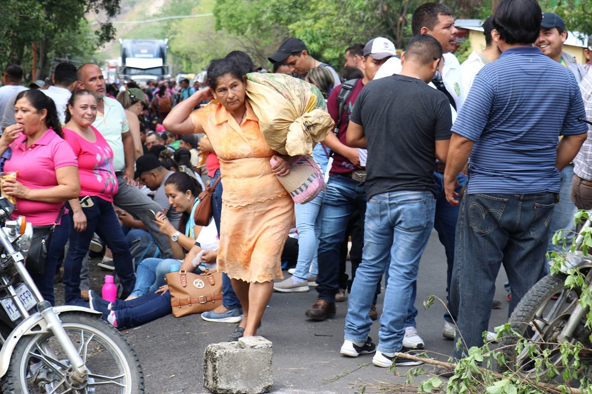 Una mujer afectada por los bloqueos carga con sus pertenencias para sortear la protesta en el km 176 de cruce a Vado Hondo, Chiquimula, y camina en medio de los maestros. (Foto Prensa Libre: Mario Morales)