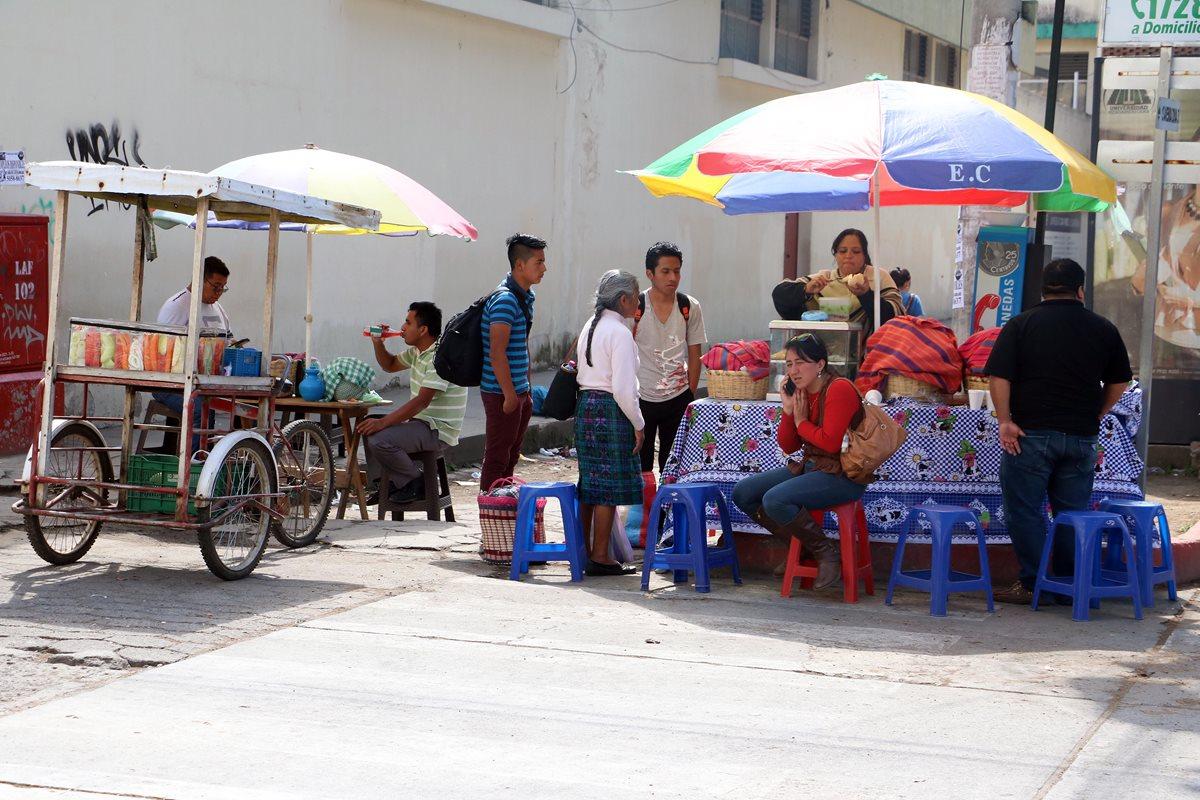 Vendedores de comida proliferan en las calles de la zona 3 de Xela, y se instalan incluso donde hay tragantes. (Foto Prensa Libre: Carlos Ventura)