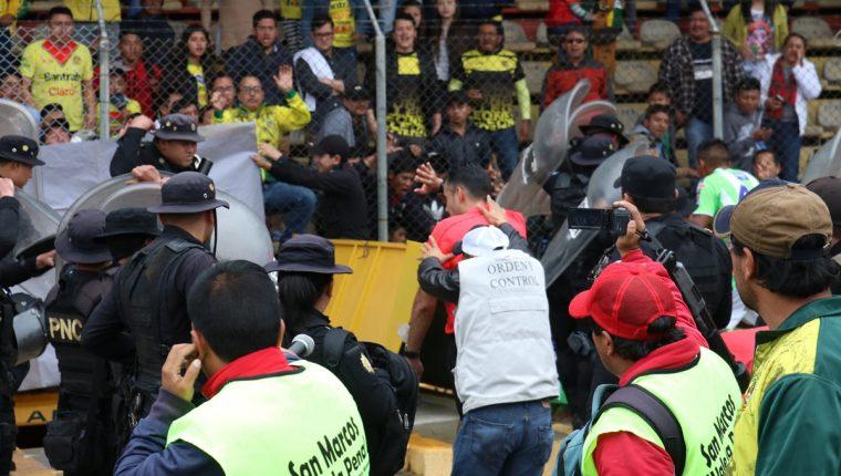 La cuarteta arbitral ingresa a los camerinos custodiada por las fuerzas de seguridad. (Foto Prensa Libre: Raúl Juárez)