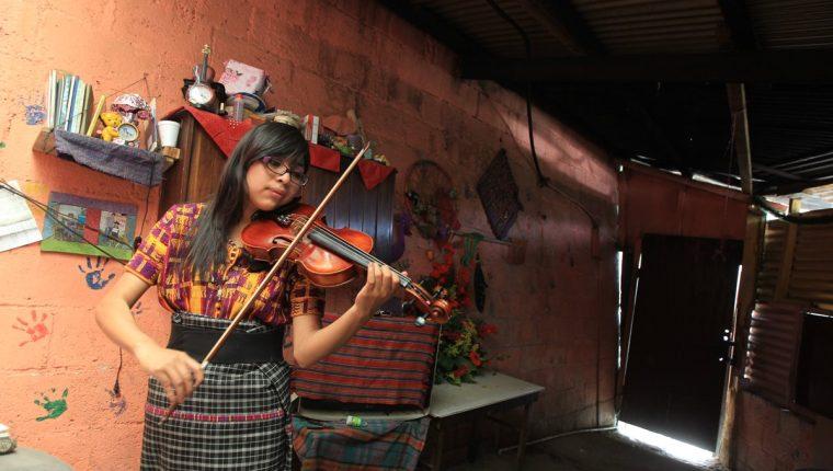 La maestra Isabel Patzán practica el violín en su vivienda antes de impartir clases privadas en comunidades de San Juan Sacatepéquez. (Foto Prensa Libre: Esbin García)