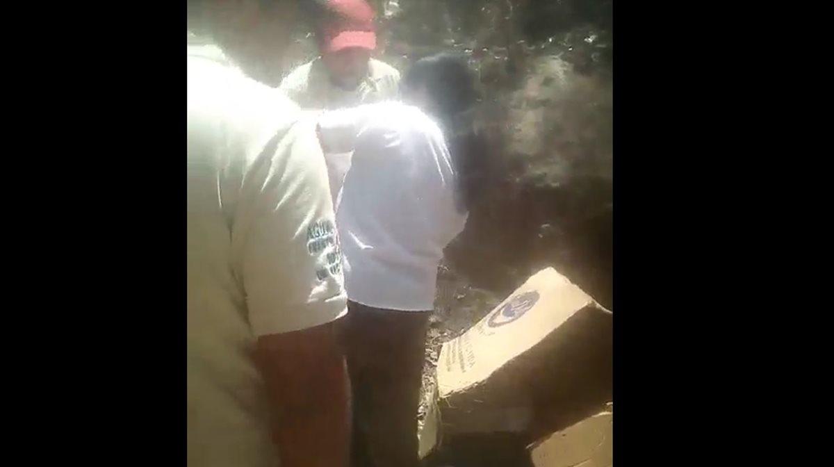 Momento en el que vecinos de la zona 10 de Huehuetenango rescatan a una bebé abandonada en un basurero. (Foto Prensa Libre: Facebook Noticiero Lasuper)
