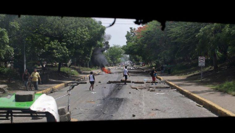 Varias personas son vistas a través de una ventana de un autobús incendiado por manifestantes en Tipitapa, a unos 25 km de Managua. (AFP).