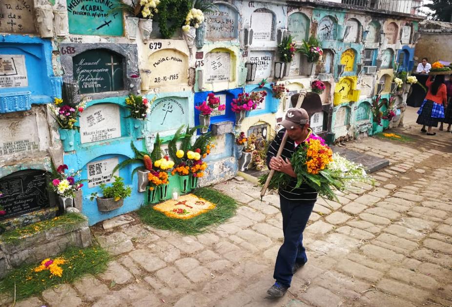 Visitante se dirige a adornar tumba en el cementerio general de Quetzaltenango. (Foto Prensa Libre: Mynor Toc).
