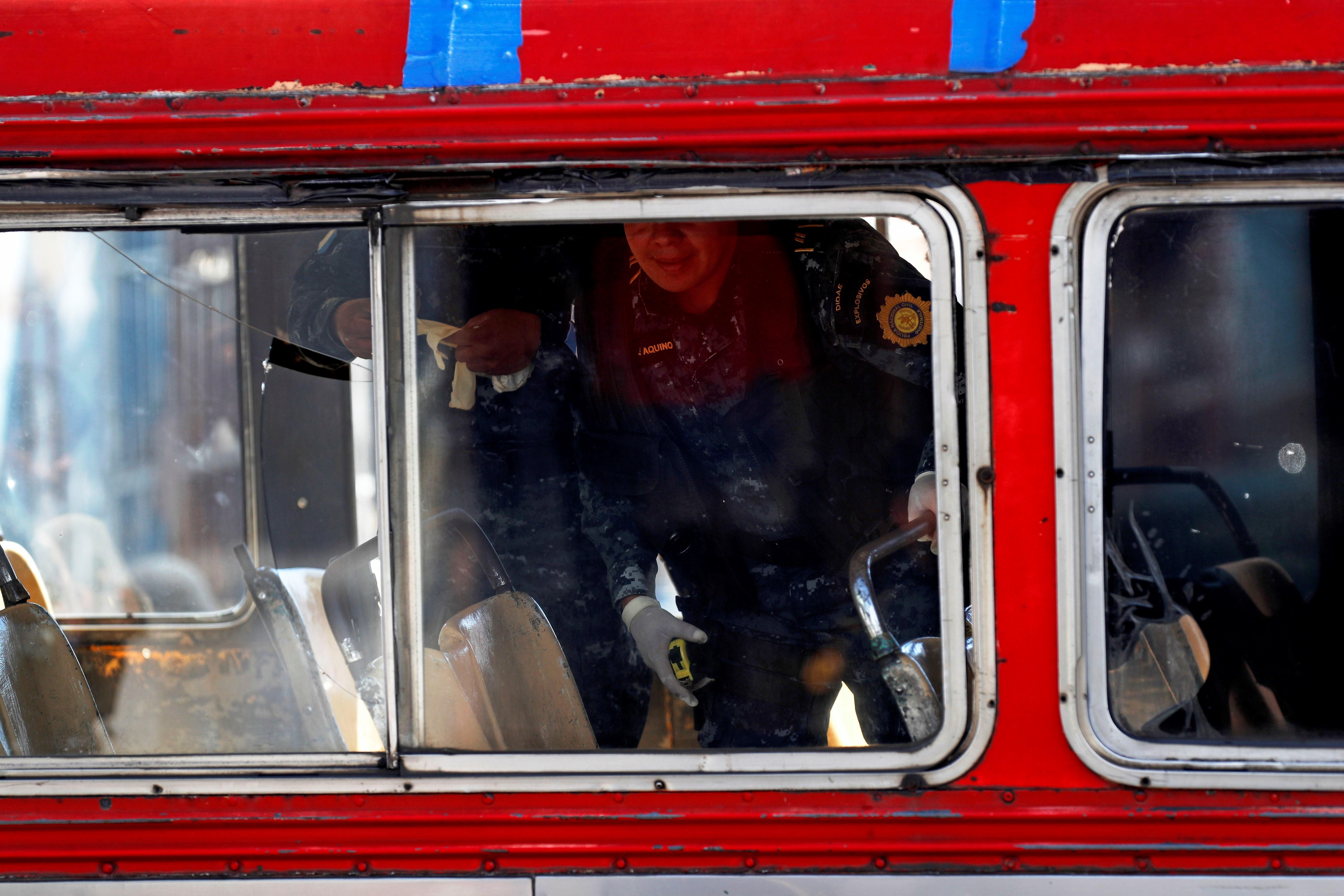 """AME584. CIUDAD DE GUATEMALA (GUATEMALA), 21/01/2019.- Policías expertos en explosivos trabajan este lunes en el lugar donde se produjo la detonación de una granada en un autobús de pasajeros, en Ciudad de Guatemala (Guatemala). Como """"fortuita"""" calificó el Gobierno de Guatemala la detonación de un artefacto en un autobús de pasajeros este lunes que dejó seis heridos, incluida la supuesta pandillera que llevaba el explosivo. El ministro de Gobernación (Interior), Enrique Degenhart, explicó en una conferencia de prensa que no era una granada de fragmentación sino un artefacto de fabricación casera que la mujer transportaba para amenazar al chófer como parte del cobro de una extorsión. EFE/Esteban Biba"""