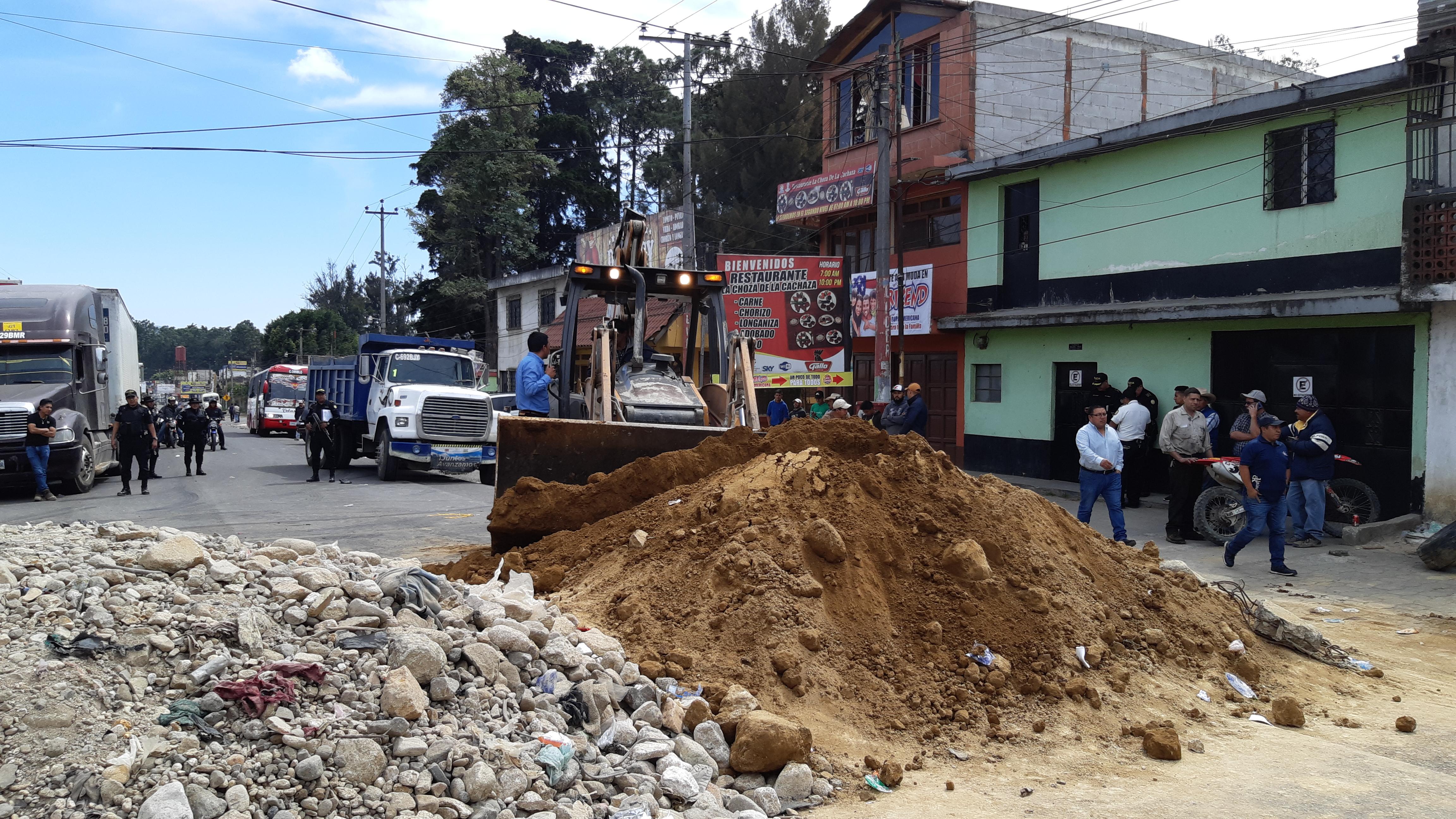 Una máquina retira el material que manifestantes colocaron en el kilómetro 56 de la ruta Interamericana para impedir la circulación de vehículos. (Foto Prensa Libre: Julio Sicán).
