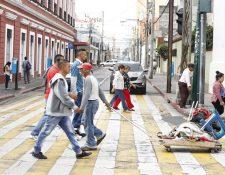 Transeúntes se desplazan por la 7a. avenida y 8a. calle de la zona 1 de la capital. (Foto Prensa Libre: Paulo Raquec).
