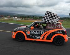 Marcos Reichert conduce su vehículo con la bandera a cuadros luego de coronarse campeón de la Copa Mini. (Foto Prensa Libre: Autódromo Pedro Cofiño)