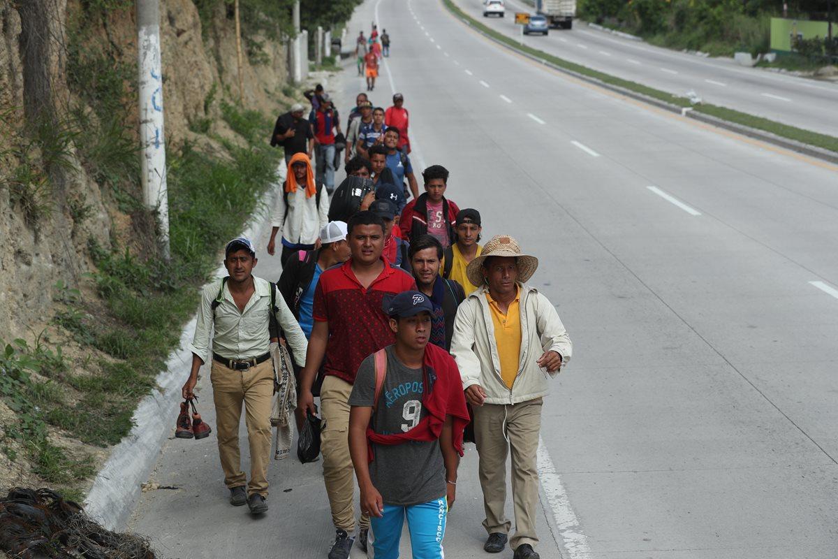 """Un grupo de migrantes camina sobre el km 50 de la ruta al Atlántico con la esperanza de encontrar a algún automovilista que les de un """"aventón"""". (Foto Prensa Libre: Esbin García)"""