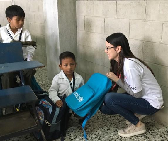 Voluntarios entregan mochilas a escolares que regresan a clases