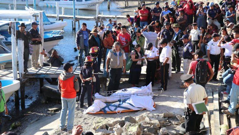 Los cuerpos de las víctimas fueron llevados a la playa pública de Panajachel, donde Fiscales del MP recaban evidencias. (Foto Prensa Libre: Yesica Medrano)