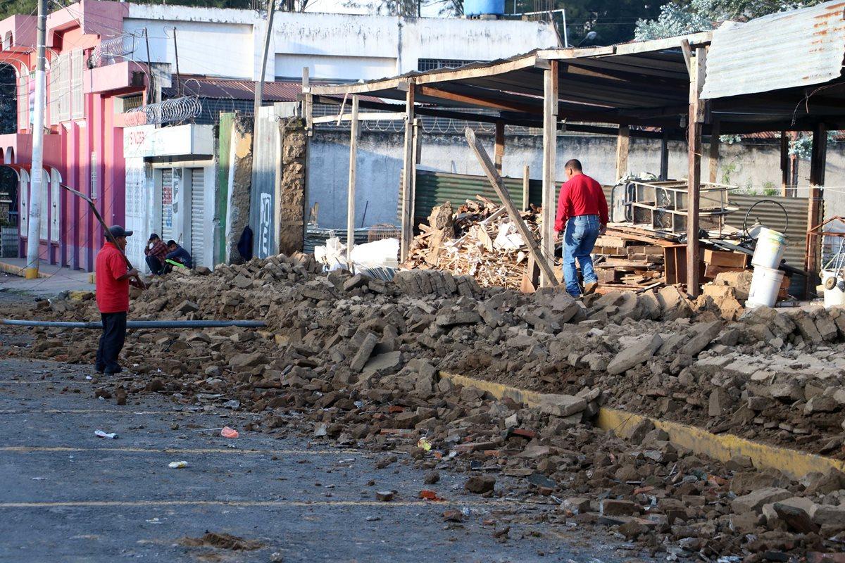 Vecinos observan la pared de un predio que se desplomo sobre la 16 avenida de la zona 3 de Xela. (Foto Prensa Libre: Carlos Ventura)