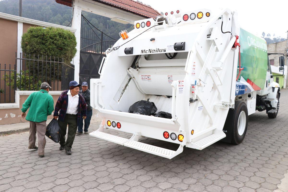 Residente de Xela y trabajadores de la comuna llevan las bolsas de basura orgánica al camión que compró la municipalidad. (Foto Prensa Libre: María José Longo).