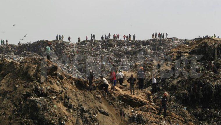 Al menos cuatro camiones recolectores de basura habrían quedado soterrados. (Foto Prensa Libre: Edwin Bercián)