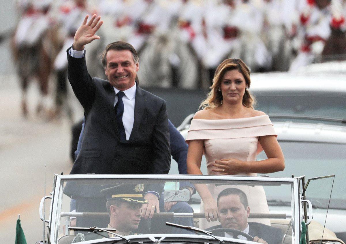 El nuevo presidente brasileño, Jair Bolsonaro, saluda junto a su esposa Michele, a bordo de un Rolls Royce en un corto recorrido para dirigirse al Palacio de Planalto, donde recibiría la banda presidencial de manos de su antecesor, Michel Temer, en Brasilia. (Foto Prensa Libre: EFE)