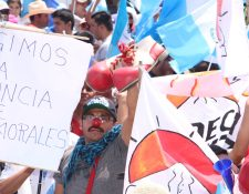Un hombre sostiene un par de zapatos de payaso y usa una nariz roja en protesta por el Gobierno de Jimmy Morales (Foto Prensa Libre: Pablo Juárez)